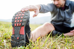 Unerkennbarer junger Läufer, der auf dem Gras, Bein ausdehnend sitzt lizenzfreies stockfoto