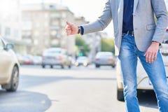 Unerkennbarer Mann-anziehendes Taxi in der Stadt stockbilder