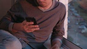 Unerkennbarer Mann betrachtet den Handy und schlägt das Band in den sozialen Netzwerken leicht, die auf dem Balkon bei Sonnenunte stock video