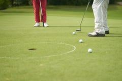 Unerkennbarer Mann, der das Golf sich setzt auf Grün spielt stockfotos