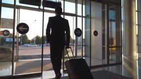 Unerkennbarer Mann, der durch automatische Glastür des modernen Flughafens zur Stadtstraße geht und Koffer auf Rädern zieht stock video
