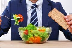 Unerkennbarer Mann isst gesunden Business-Lunch im modernen Büro zu Mittag Lizenzfreie Stockfotos