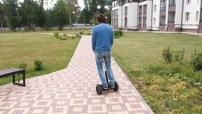 Unerkennbarer Mann rollt auf Kreiselkompassroller nahe dem Haus, hintere Ansicht stock footage