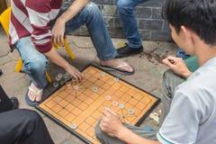 Unerkennbarer Mann spielt das traditionelle Brettspiel, das als chinesisches Schach bekannt ist stockbilder