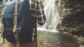 Unerkennbarer Reisender mit Rucksack erreichte seins und Stände auf der Wasserfall-Hintergrund-Nahaufnahme, die Reise-Reise-Wande Stockfoto