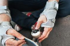 Unerkennbarer Schlittschuhläufer überprüft sein Skateboard stockfotos