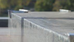 Unerkennbarer Schlittschuhläufer tut den Schleifentrick, der auf granit Leiste, Nahaufnahmeansicht gekrümmt ist stock footage