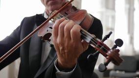 Unerkennbarer Violinist im Kostüm, Mann übergibt Spiele auf einer hölzernen Geige stock video