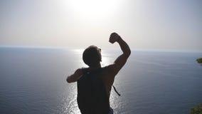 Unerkennbarer Wanderer mit freuender Erfolgsstellung des Rucksacks auf Rand der Spitze männlicher Tourist, der aktiv während der  stock video footage