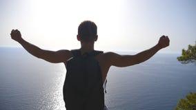 Unerkennbarer Wanderer mit Rucksackstellung auf Rand des Berges und victoriously der anheben Hände Männlicher Tourist aktiv stock video