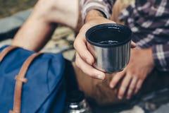 Unerkennbarer Wanderermanngetränktee oder -kaffee von der Thermosflasche, Nahaufnahme Wandern und Freizeitthema Stockfoto