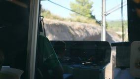 Unerkennbarer Zugfahrer fährt elektrischen Zug unter Gebirgsstraße Gesichtspunkt von Fahrerhaus zu Eisenbahn stock footage