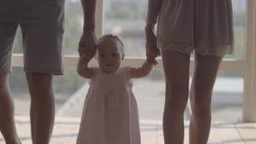 Unerkennbares gehendes Händchenhalten des Mannes und der Frau des netten Babys zu Hause Das Kind, das zuerst Schritte mithilfe ma stock video footage