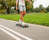 Unerkennbares Mädchen, das auf ein longboard eisläuft Lizenzfreie Stockfotografie