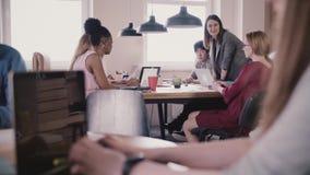 Unerkennbares Mädchen, das auf Laptop schreibt Gedanklich lösen durch die Tabelle im modernen multiethnischen Dachbodenbüro im Hi stock video footage