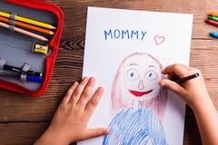 Unerkennbares Mädchenzeichnungsbild ihrer Mutter Hölzernes backgr lizenzfreies stockfoto