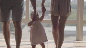Unerkennbares Mann- und Frauenhändchenhalten des netten Babys zu Hause Das Kind, das zuerst Schritte mithilfe der Mutter macht stock video