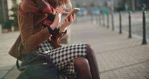 Unerkennbares Porträt der kaukasischen Frau, die Telefon in einer Stadt verwendet Lizenzfreie Stockfotografie