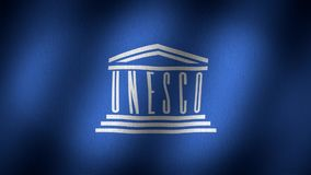 Unesco flag. Animated, waving flag composed by a greek temple whit the UNESCO inscription as pillars of it, all over a navy blue back, fabric texture background stock video