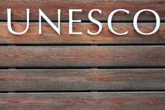 UNESCO text on brown background. UNESCO text on brown wood background Stock Photography
