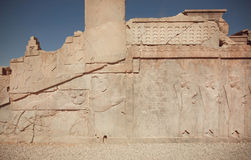 UNESCO World Heritage Site, carved animals and wariors on historical walls of ruined palace of Persepolis Stock Image