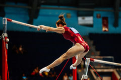 Uneven bars female gymnast. To competition in artistic gymnastics royalty free stock photo
