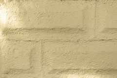 Uneven brick wall texture outside tan-1 royalty free stock image