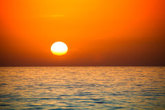 Uneven disk of the sun setting over the horizon Stock Image