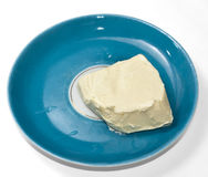Uneven piece of butter on a saucer Royalty Free Stock Photography