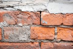 Uneven red brick wall. In the cracks stock image