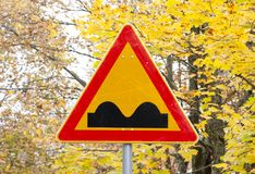 Uneven Road Sign on yellow autumn leaves background. Uneven Road Sign on yellow autumn leaves background Royalty Free Stock Images