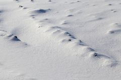 Uneven soil. Covered with pure snow after a snowfall, close-up in a frosty morning stock photography