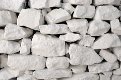 Uneven White Stone Wall. Wall made of white stones piled on top of one another in a disorderly fashion. Background Texture stock photos