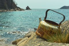 Old rusty tea on a turquoise sea background. kettle on the journey. royalty free stock photos