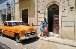 An unexpected meeting of Europe and Cuba. Cuba, Havana - 07 April, 2016: a European woman waiting for the driver of the taxi in Havana to bring her to the needed Stock Image