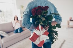 Unexpected moment in routine everyday life! Cropped photo of man. `s hands hiding holding chic bouquet of red roses and gift with white ribbon behind back, happy Stock Image