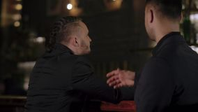Two men in suits drink whiskey in a bar. Unexpected, pleasant meeting of two men in a bar, where one of them drinks whiskey. At the sight of each other they stock video