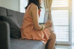Unexpected pregnancy concept,Asian woman sitting at house,Female feeling unhappy and confused problem alone,Selective focus hands. Unexpected pregnancy concept stock photo