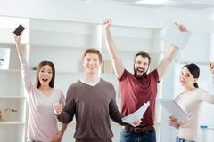 Cheerful four colleagues celebrating promotion. Unexpected promotion. Joyful nice four colleagues gesturing  while feeling success  and screaming Royalty Free Stock Photos