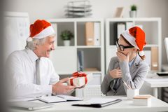 Unexpected surprise. Aged boss in Santa cap giving small box with xmas surprise to one of his subordinates during work Royalty Free Stock Photos