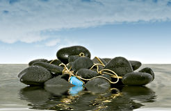Unexpected Treasure. Pendant with gold chain found entangled in rocks on the shore Royalty Free Stock Images