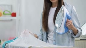 Unexperienced female making hole in blouse during ironing, house work problems. Stock footage stock footage
