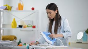 Unexperienced housewife holding iron and burned blouse, looking at camera. Stock footage stock footage