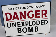 Unexploded bomb sign. Old, antique London police sign warning of danger from an unexploded WWII bomb Stock Photo
