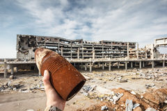Unexploded 120 mm shell in hand with airport ruins Stock Image