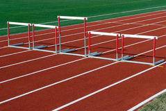 Unfair competition. Hurdles of different sizes on race track Stock Images