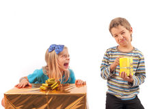 Unfair gift giving - siblings. Unfair gift giving between siblings: the girl with big present box is gloating because her brother has only a very small gift box Stock Photography