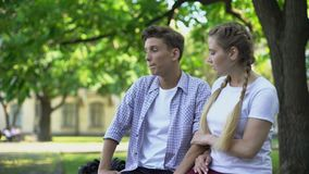 Unfaithful boyfriend looking at pretty woman passing by, girlfriend noticing it. Stock footage stock video