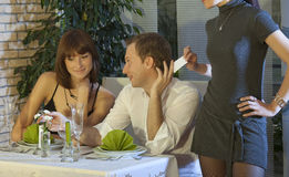 Unfaithful man cheating in restaurant Stock Photos