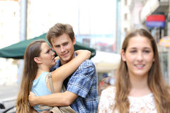 Unfaithful man hugging his girlfriend and looking another Royalty Free Stock Photos